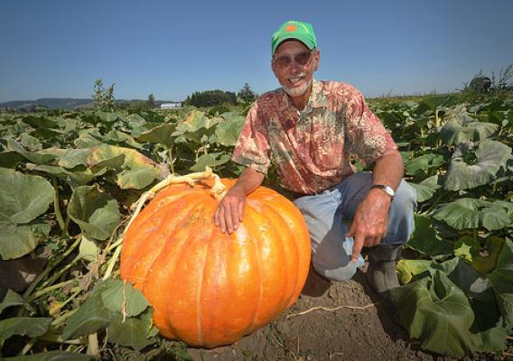 Farmer David Brown poses next to one of his giant pumpkins. Healthy soil is key to the success of Mustard Seed Farms. Photo courtesy of NRCS.