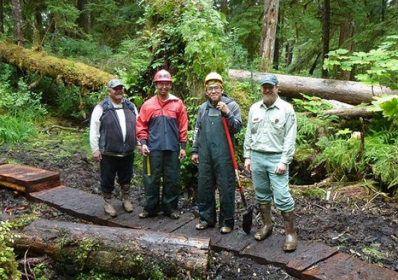 A new foot bridge near the tribal village of Angoon on Admiralty Island National Monument is part of a Tongass National Forest and Youth Conservation Corps partnership. From left, Tribal Liaison Donald Frank, Angoon Trail Crew Leader Aaron McCluskey, Youth Conservation Corps member Roger Williams, also an Angoon tribal member, and Admiralty Island National Monument Ranger Chad VanOrmer pause work to celebrate the bridge's construction and the agency's successful Corps partnership with the Angoon Tribe. (U.S