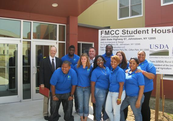 Deputy Under Secretary for Rural Development Doug O'Brien (left) with students from Fulton Montgomery Community College.  The group is standing in front of the new, USDA-funded dormitory.