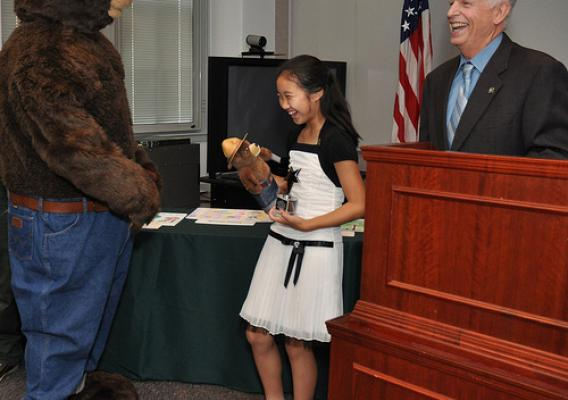 Smokey Bear presents Caroline Tan, 11, with a replica of himself during a ceremony led by U.S. Forest Service Chief Tom Tidwell to honor the Westfield, N.J., girl as the national winner in the 2012 Smokey Bear & Woodsy Owl Poster Contest. Caroline's winning poster was chosen from nearly 22,000 entries. Dominic Cumberland/U.S. Forest Service Photo