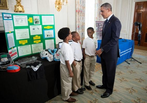 President Barack Obama talks with Evan Jackson, 10, Alec Jackson, 8, and Caleb Robinson, 8, from McDonough, Ga., while looking at exhibits at the White House Science Fair in the State Dining Room, April 22, 2013. The sports-loving grade-schoolers created a new product concept to keep athletes cool and helps players maintain safe body temperatures on the field. (Official White House Photo by Chuck Kennedy)