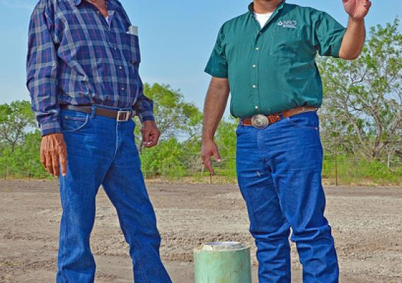 Rancher Willie Utley of Benavides, Texas and Sammy Guerra, USDA Natural Resources Conservation Service district conservationist in Benavides, Tex., discuss the successful drilling of the water well they're standing behind. (NRCS photo/Beverly Moseley)