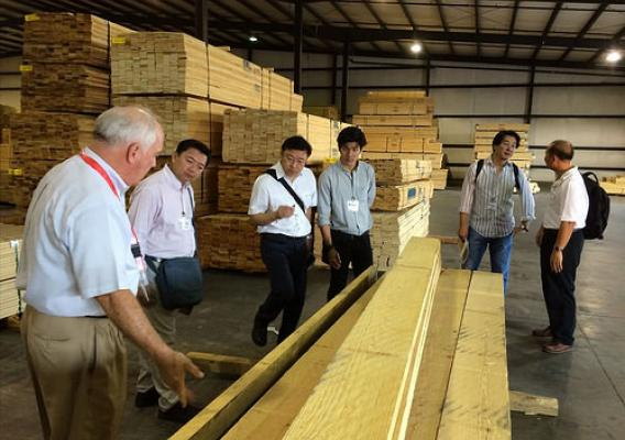 A delegation of Thai lumber company executives (including Opas Panitchewakul, Pracha Thawornjira, Jaroonsak Cheewatammanon, Khomwit Boonthamrongkit and Wasant Sonchaiwanich) tours the Mauvila Timber distribution warehouse in Loxly, Ala., with Lane Merchant (left), the company's general manager.