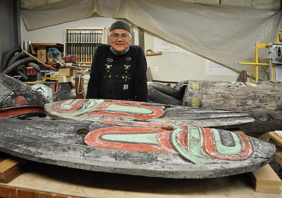 Tlingit Master Carver Wayne Price of Haines stands near the totem he is restoring. The totem has overlooked the Auke Recreation Area for more than 70 years. (U.S. Forest Service photo by Laurie Craig)