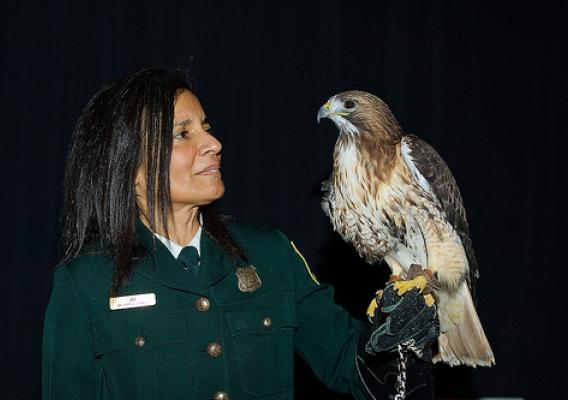 Jo Santiago, a U.S. Forest Service Wildlife Biologist with a red-tailed hawk