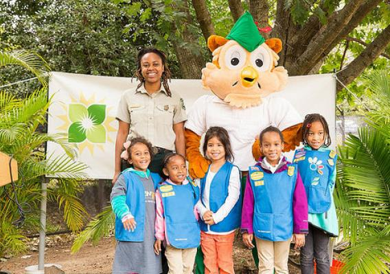 A Forest Service employee, along with Woodsy Owl, pose with kids from the Girl Scott's Daisy program during National Public Lands Day (Photo Credit: US Forest Service.)